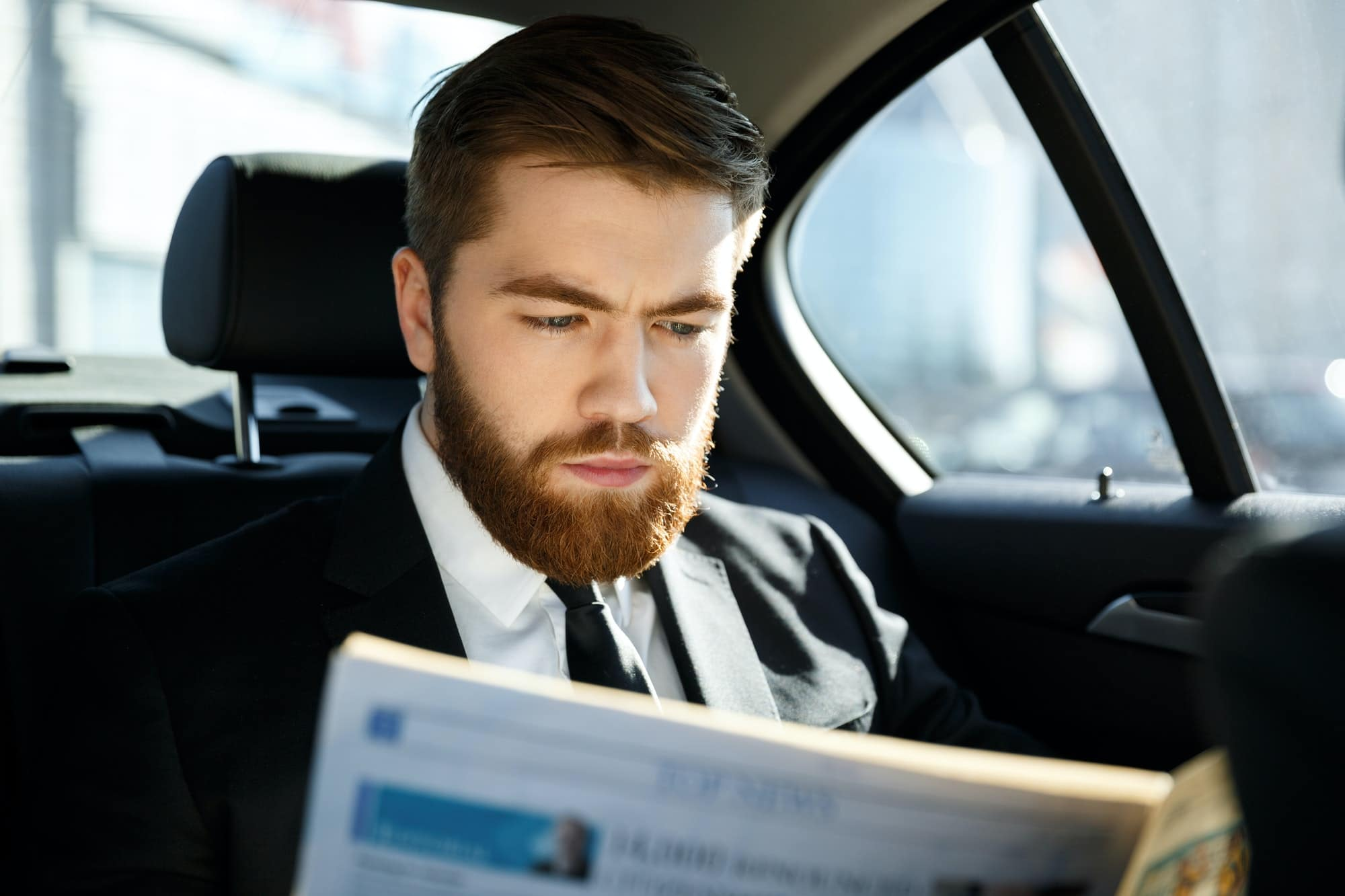 Concentrated business man reading newspaper