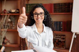 Woman wearing headphones, showing thumbs up gesture